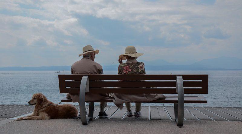 pareja de ancianos sentados en un banco mirando al mar